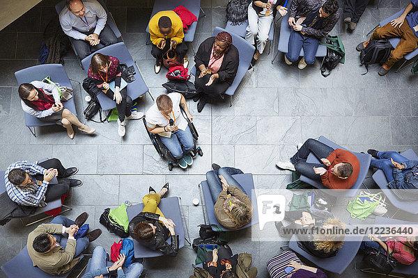Overhead-Ansicht Konferenzpublikum beim Hören des Sprechers im Rollstuhl
