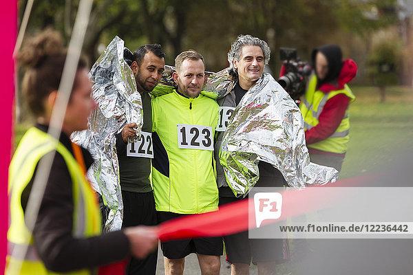 Männliche Marathonläufer in Thermodecke im Ziel eingewickelt