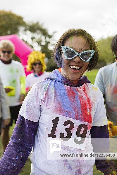 Portrait verspielte Läuferin mit Sonnenbrille und holi powder beim Charity-Lauf im Park