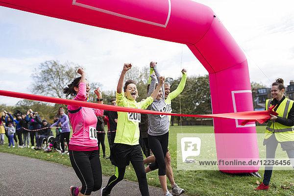 Enthusiastische Familienläufer überqueren die Ziellinie des Charity-Laufs im Park