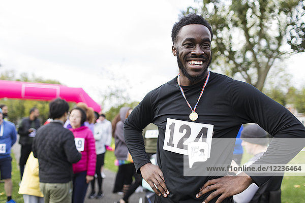 Portrait glücklicher  selbstbewusster Läufer mit Medaille beim Charity-Lauf im Park