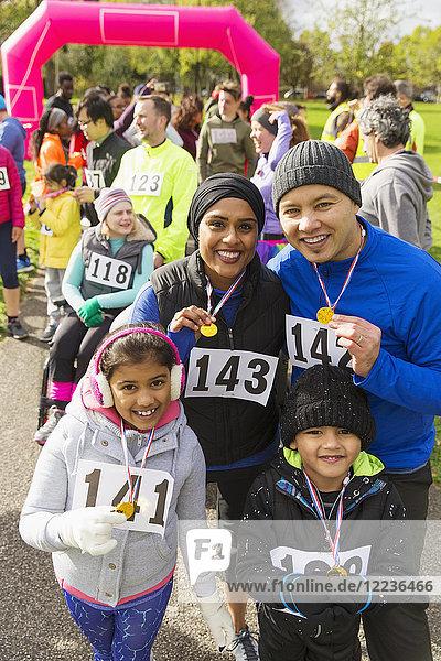 Portrait lächelnde Familie mit Medaillen beim Benefizlauf