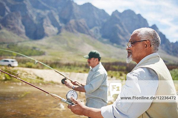 Aktive Seniorenfreunde beim Angeln am sonnigen Sommerseeufer