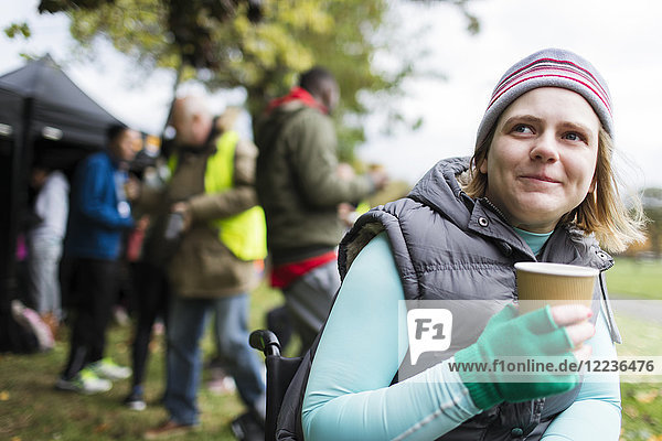 Frau im Rollstuhl beim Kaffeetrinken im Park