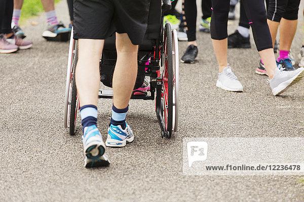 Mann schiebt Rollstuhl auf überfülltem Weg