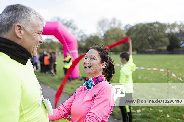 Glückliche Läufer überqueren die Ziellinie beim Charity-Lauf im Park