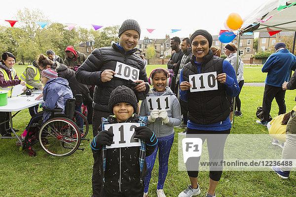 Porträt selbstbewusste Familienläufer mit Marathon-Lätzchen beim Charity-Lauf im Park