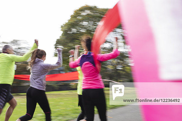 Enthusiastische Familienläufer überqueren die Ziellinie beim Benefizlauf im Park