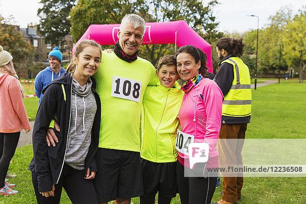 Porträt lächelnde Familienläufer beim Benefizlauf im Park