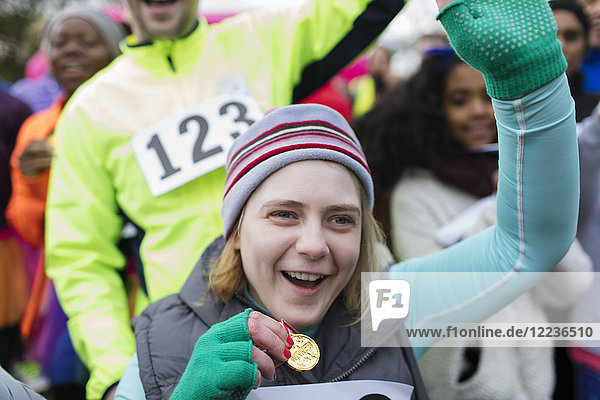 Enthusiastische Frau mit Medaillenjubel beim Charity-Rennen