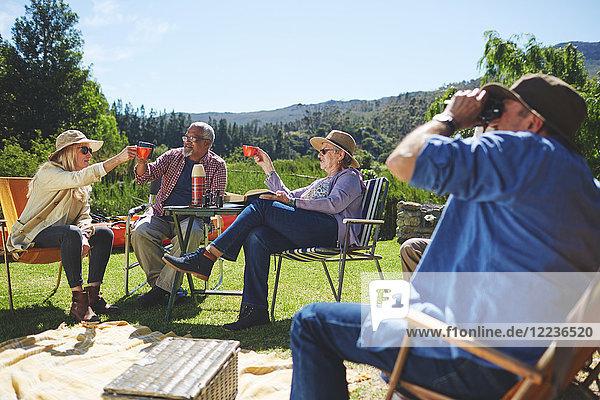 Aktive Seniorenfreunde beim Kaffeetrinken auf dem sonnigen Sommercampingplatz