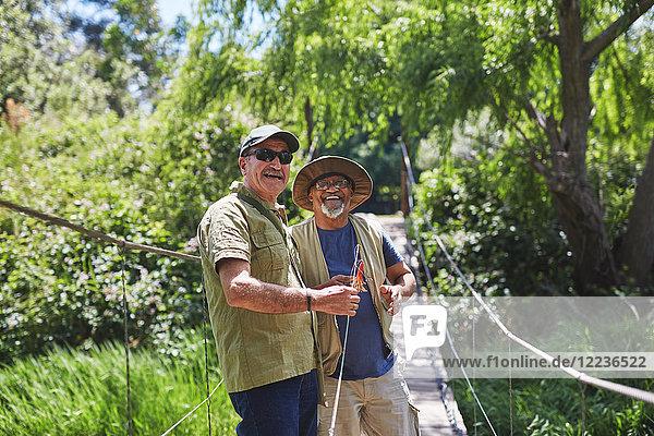 Portrait fröhlich aktive Senioren Freunde fischen auf sonniger Sommer-Fußgängerbrücke