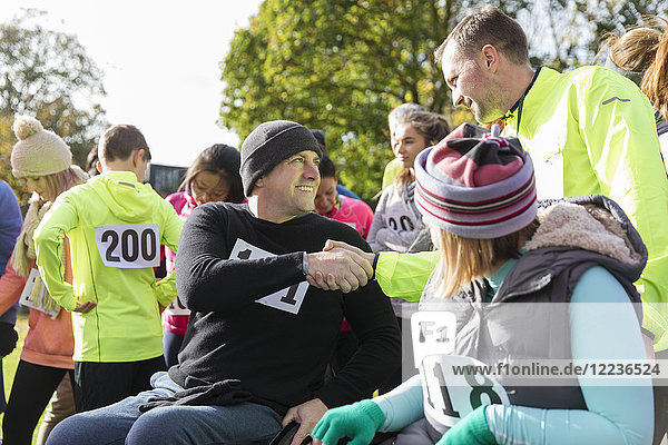 Läufer schüttelt Hände mit Mann im Rollstuhl beim Charity-Rennen im sonnigen Park