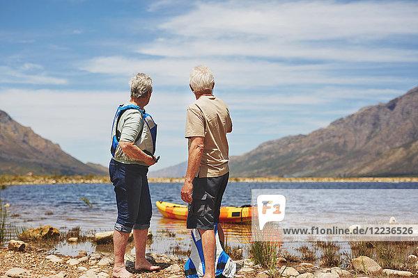 Aktives Seniorenpaar beim Kajakfahren am sonnigen Sommersee