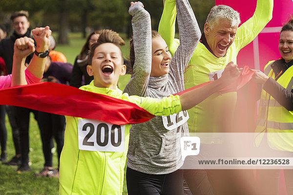 Enthusiastischer Läufer  der mit seiner Familie über die Ziellinie läuft.
