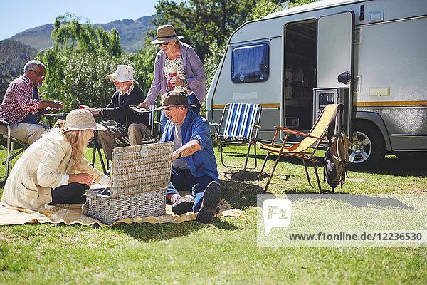Aktive Seniorenfreunde genießen ein Picknick vor dem Wohnmobil auf dem sonnigen Sommercampingplatz.