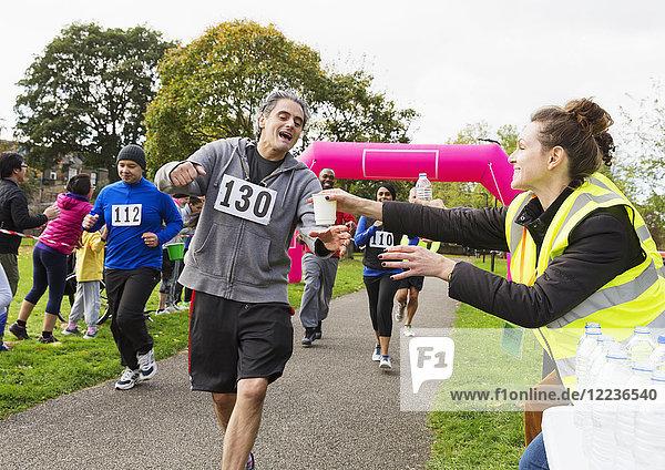 Freiwillige Wasserspende an Läufer beim Benefizlauf im Park
