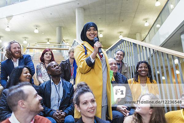 Lächelnde Frau im Hijab spricht mit Mikrofon im Konferenzpublikum