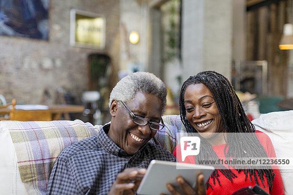 Adult Tochter Lehre Senior Vater  wie man digitale Tablette auf dem Sofa verwenden