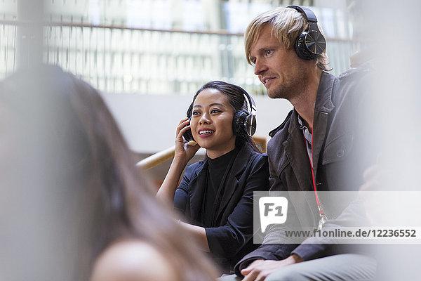 Lächelnde Geschäftsleute mit Kopfhörern im Konferenzpublikum