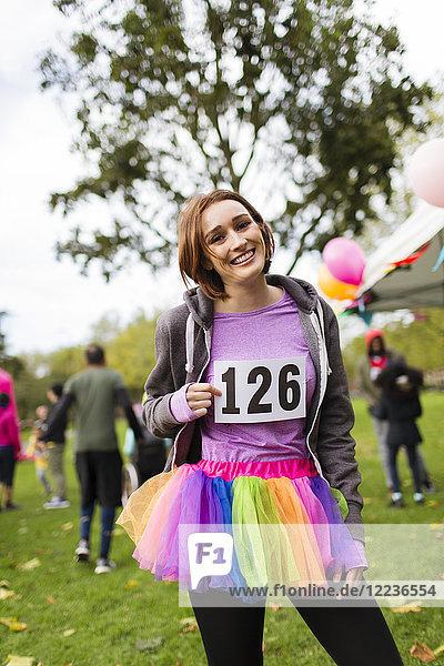 Portrait lächelnde  selbstbewusste Läuferin im Tutu beim Charity-Lauf im Park