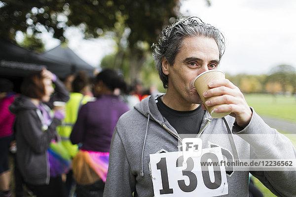 Männlicher Marathonläufer Trinkwasser im Park