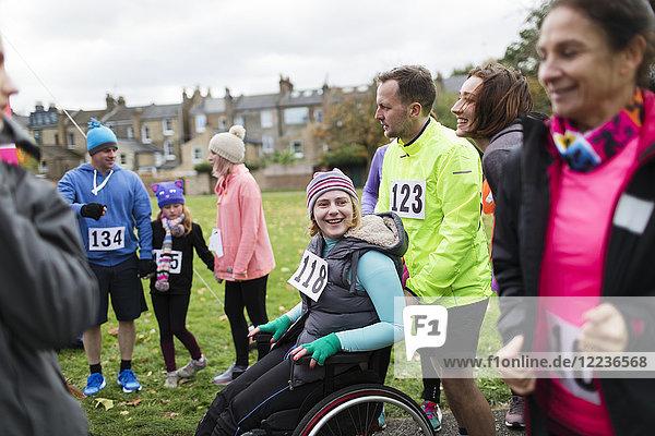 Mann schiebt Frau im Rollstuhl beim Charity-Rennen im Park