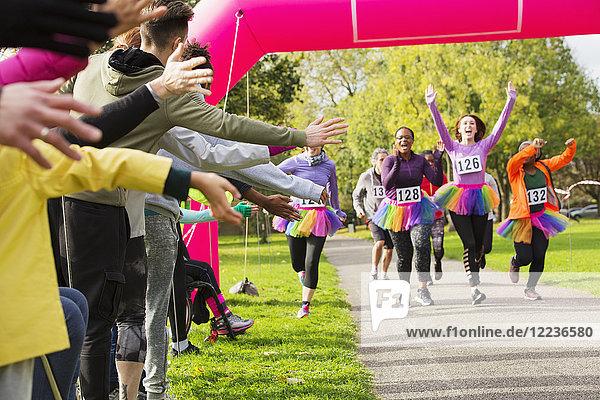 Enthusiastische Läuferinnen im Tutus beim Charity-Lauf im Park im Ziel