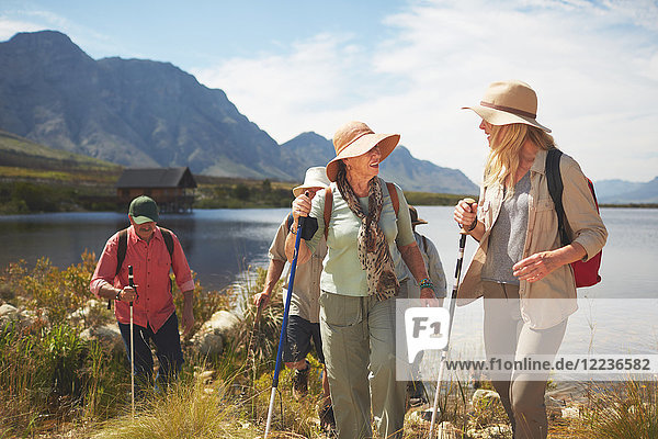 Aktive Seniorinnen wandern entlang des sonnigen Sommersees