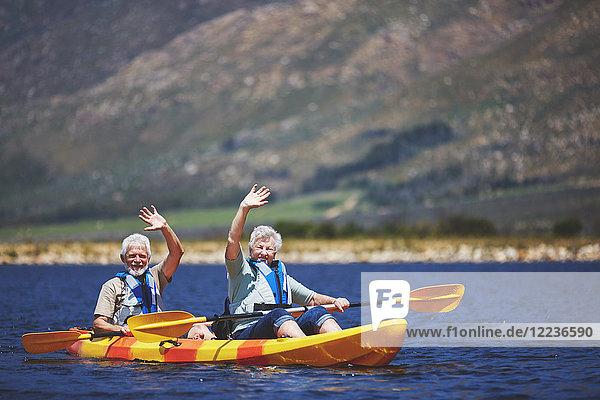 Porträt eines aktiven Seniorenpaares im Kajak auf dem sonnigen Sommersee