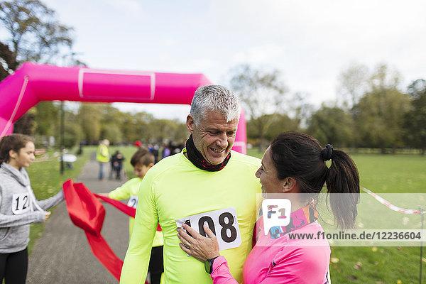 Glückliche Läuferinnen und Läufer umarmen sich am Ziel beim Charity-Lauf im Park