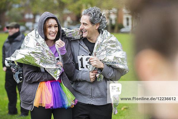 Glückliche Paarläufer in Thermodecke gewickelt beim Benefizlauf im Park