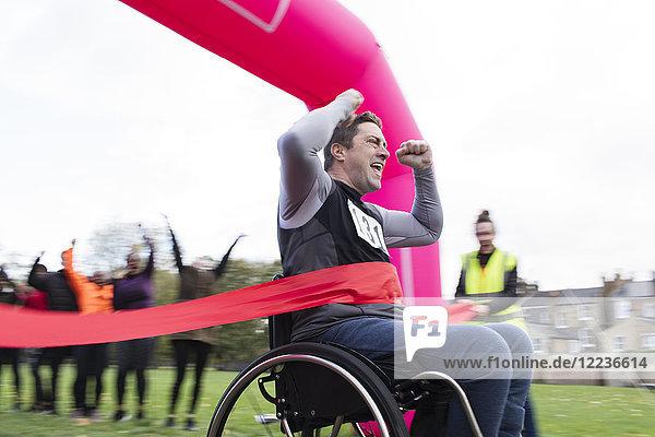 Enthusiastischer Mann im Rollstuhl überquert die Ziellinie  jubelt beim Charity-Rennen im Park.