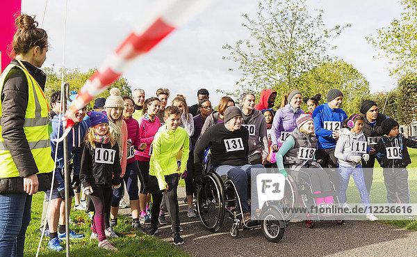 Viele Läufer und Rollstuhlfahrer warten an der Startlinie des Charity-Rennens.