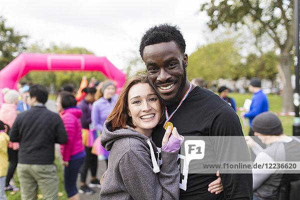 Porträt glückliche Paarläufer mit Medaille beim Benefizlauf im Park