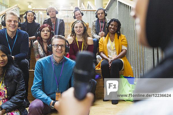 Lächelndes Publikum mit Kopfhörer und Konferenzlautsprecher Lächelndes Publikum mit Kopfhörer und Konferenzlautsprecher