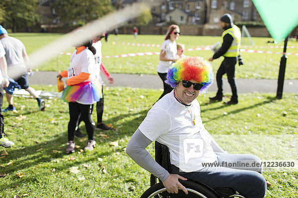 Portrait lächelnder  verspielter Mann im Rollstuhl mit Clown-Perücke beim Charity-Rennen im sonnigen Park