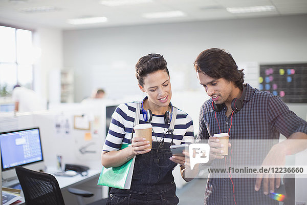 Creative business people drinking coffee and using smart phone in office