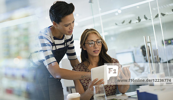 Creative businesswomen using smart phone and digital tablet in office