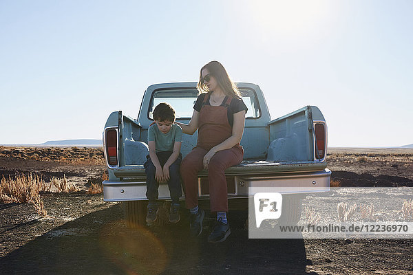 USA  Arizona  Mother comforting son (6-7) on tailgate of pick-up truck