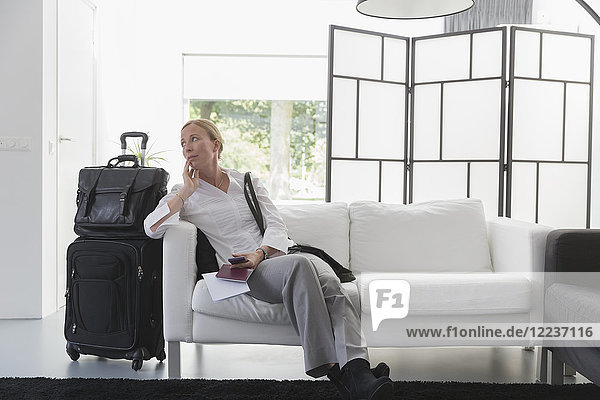 Mature woman waiting with luggage in modern living room