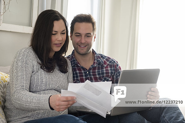 Mid adult couple sitting on sofa and looking at letter  man holding laptop