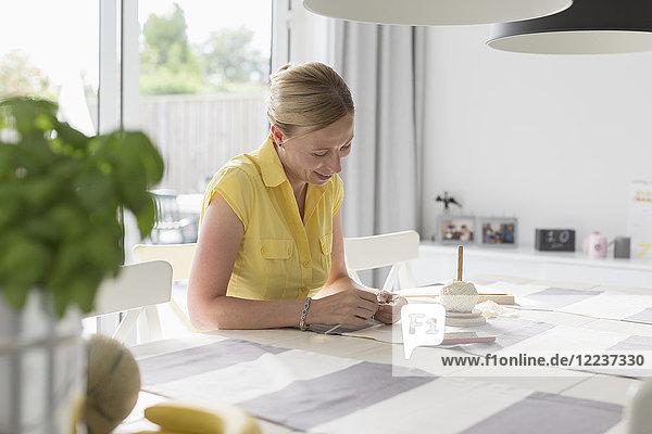 Mature woman making macrame at table