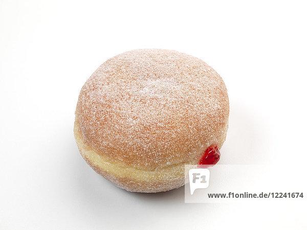 Ein Krapfen mit roter Marmeladenfüllung vor weissem Hintergrund