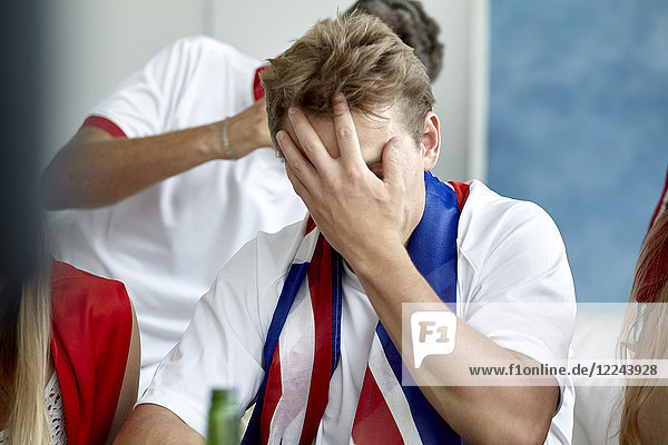 Britischer Fußballfan  der das Gesicht mit der Hand bedeckt  während er sich das Spiel ansieht.