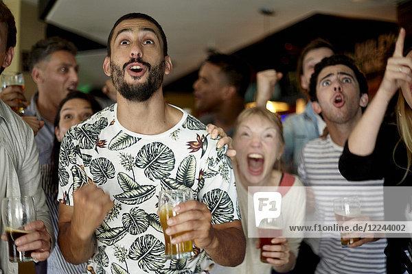Sportbegeisterte sehen das Spiel in der Bar mit Spannung.