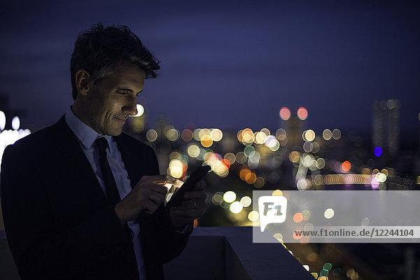 Geschäftsmann auf dem Hochhausdach mit Handy