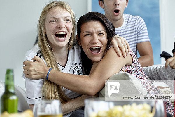 Fußballbegeisterte umarmen sich und lächeln fröhlich  während sie das Spiel zu Hause verfolgen.