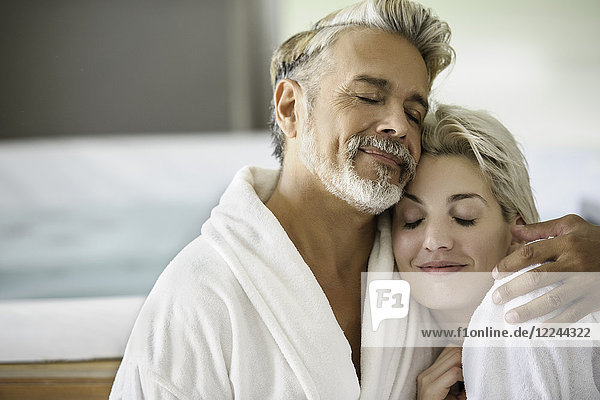 Couple in bathrobes embracing