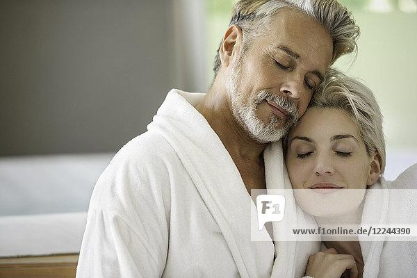 Paar im Bademantel umarmend